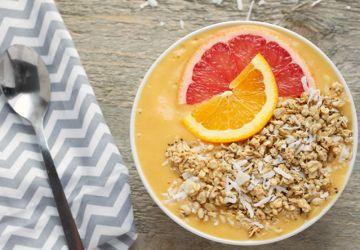 Bol déjeuner de smoothie tropical végan avec granola à la noix de coco et au chanvre