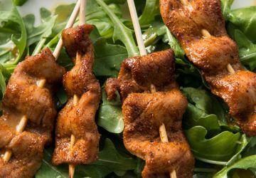 Brochettes de porc aux épices sur salade de roquette